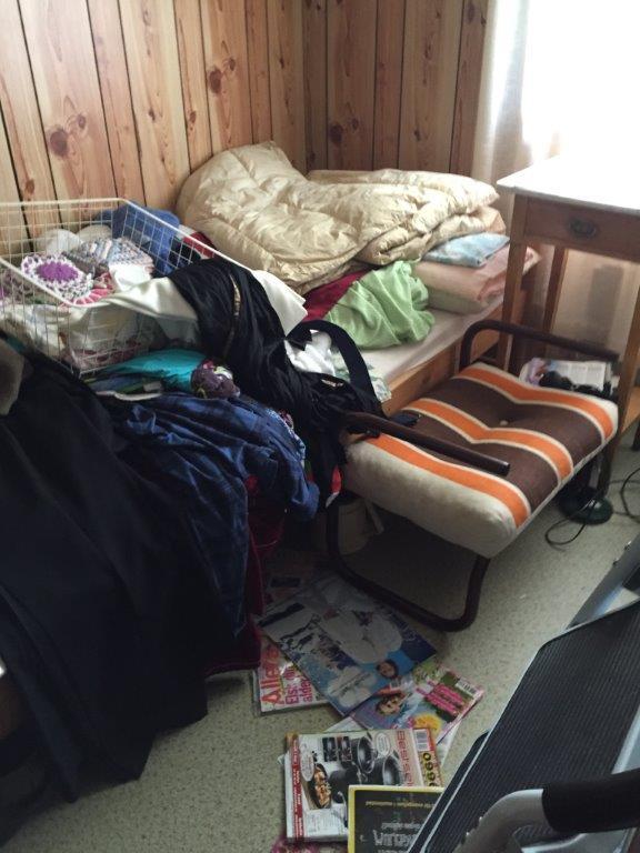 Enden av sengen på mitt rom. Ingen av møblen i rommet er synlige, bare et nattbord i bjørk med marmorplate, En stappfull bokhylle til høyre og to breddfulle gulv-til-tak stativer med ti skuffer i hver til venstre kan ikke ses. Det sto også et par ekser og en bærepose med ting klare til avhenting ved foten av sengen. 03_-2015-06-22-12.12.58
